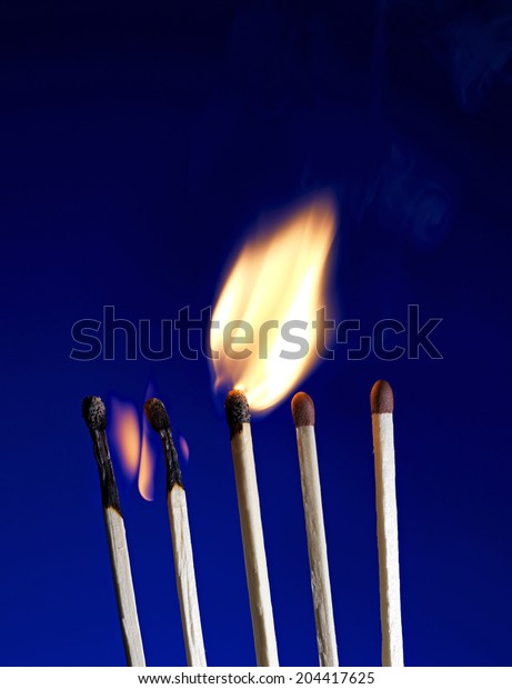 Macro shot of a flaming matchstick on blue