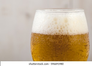 macro shot of fresh cold glass of beer with foam