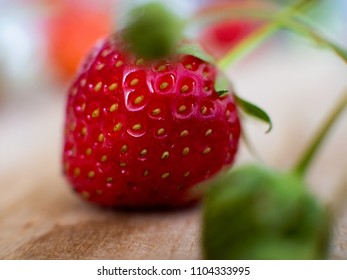 Macro Shot of a fresh homegrown strawberry on a wooden board