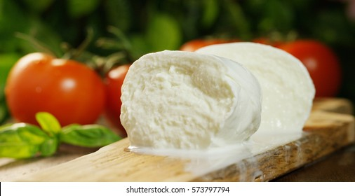 macro shot of a fresh Italian mozzarella di bufala and bio full of milk and the background with red tomatoes and basil. Concept: milk, fresh, pizza, Italian.