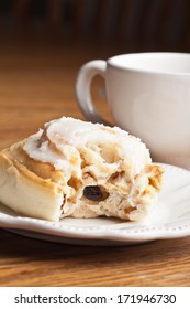Macro shot of a freshly made cinnamon roll with a bite out of it next to a vintage antique cup of hot wassail