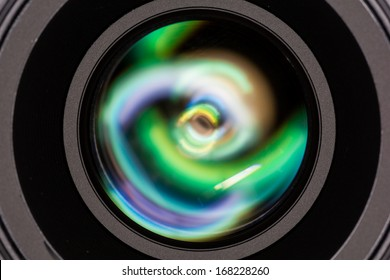 Macro shot of front element of a camera lens with beautiful color lights reflections