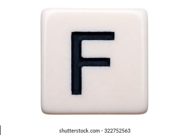 A macro shot of a game tile with the letter F on it on a white background.