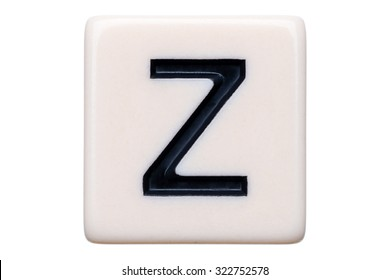 A macro shot of a game tile with the letter Z on it on a white background.