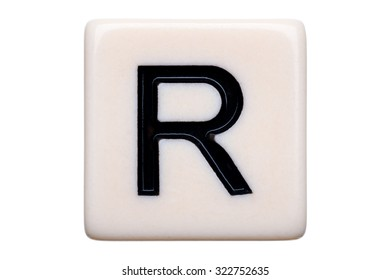 A macro shot of a game tile with the letter R on it on a white background.