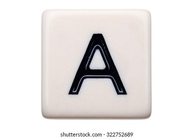 A macro shot of a game tile with the letter A on it on a white background.