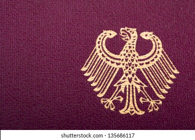 """A macro shot of the German """"coat of arms"""" printed on a German passport cover. The coat of arms of Germany is a sign of Germany; the coat of arms features an eagle."""