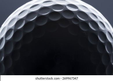 Macro shot of golf ball with dark empty space for text.