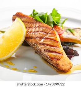 Macro shot of grilled salmon steak with bbq vegetables, fresh greens and spices closup. Barbecue red trout fish fillet decorated with spicy greens on white restaurant plate isolated
