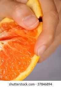 Macro shot of a hand tearing an orange peel off