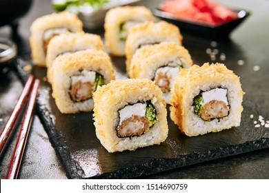 Macro shot of hot crispy ebi tempura maki sushi rolls with cream cheese, king prawn, chuka kelp salad and nori. Deep fried uramaki roll set on natural black stone slate background closeup