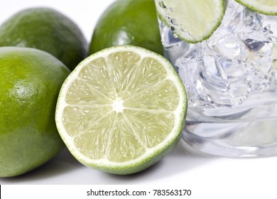Macro shot of limes and drink with focus on cut lime.