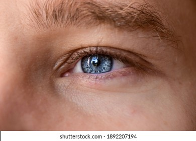 Macro shot of man's blue eye with visible blood vessels. Close-up portrait of a young man with blue eyes - OBS: model use lens contact Ophthalmology. Selective focus. Defocused