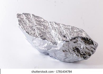 Macro shot of nickel metal ore piece isolated on a white background. Closeup photo of surprising shiny rough mineral, chrome stone, used in industry