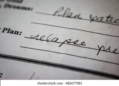 """Macro shot of nurse's handwriting on paper. Focus on word """"relapse"""""""