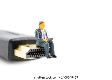 Macro shot on miniature figure as business man working on the laptop notebook sitting on HDMI plug, isolated on white background. Information technology IT and business concept