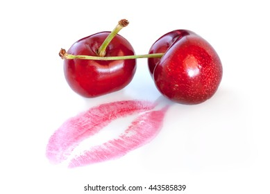 A macro shot of a pair of cherries beside the purple imprint of a lip