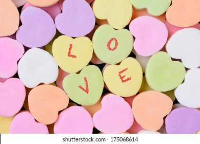 Macro shot of pastel candy hearts for Valentine's Day. Four of the candies have the word LOVE spelled out in individual letters.