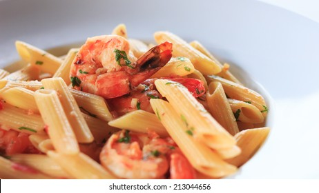 Macro shot of penne with shrimps and garlic on white plate.