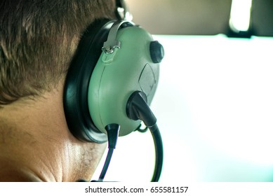 Macro shot of pilot wearing aviation headset and flying with small plane and talking with dispatcher. Ready to take off to carry passengers to another city. Flying high above clouds.