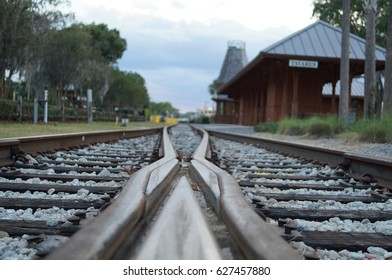 Macro shot of rail road crisscross track switch with station in background