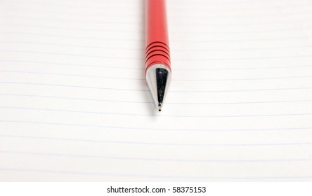 macro shot of red pencil on lined sheet