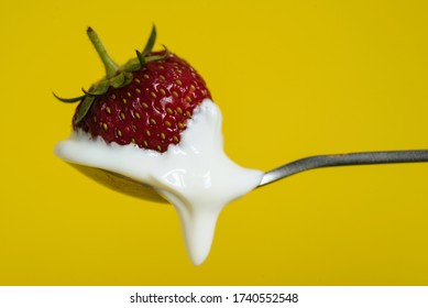 Macro shot of ripe strawberries on a spoon with sour cream. Closeup red berry with yellow background