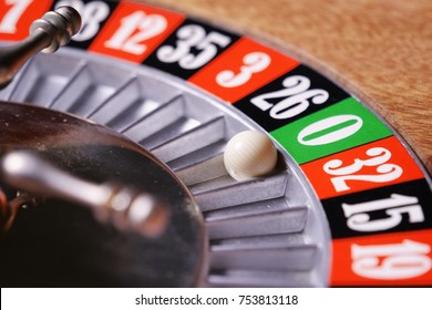 Macro shot of a roulette in a casino where the ball goes to the green or red or black number. People having bet and bet money may have won lost badges. Concept of: fate, gambling, luck, destiny.