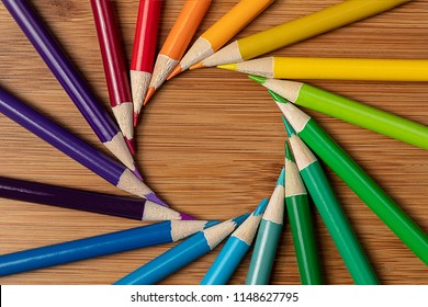 A Macro Shot of Sharpened Colored Pencils in a vortex spiral pattern on a bamboo table.  Colors follow the color and shade pattern of a standard color wheel. There is room for Copy work in the center.