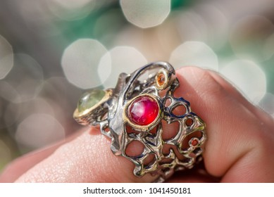 Macro shot of silver engagement ring on colorful, sparkling background. Wedding ring with prehnite stone, ruby and sapphire crystals. Royal, expensive and luxury gift