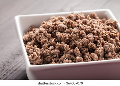 Macro shot of small white bowl of cooked ground meat on brown wooden table