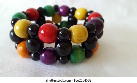 A macro shot of some colored round wooden beads made into a handmade wristband. Red, green, yellow, purple, orange, and black beads make up this spectacular ladies hand accessories.