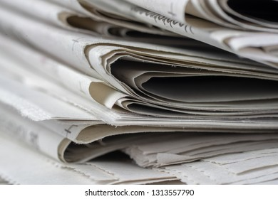 Macro shot of a stack of newspapers. The newspapers are folded and the articles are not legible