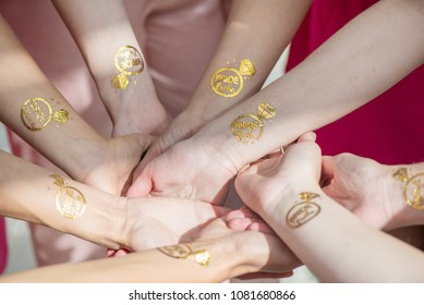 Macro shot of temporary tattoo of a ring on bridesmaids hands held together. Cheerful bride and bridesmaids party before wedding. Women having fun