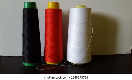 A macro shot of three big cones of thread standing like pillars side by side. One black, one red and the last white. Thread usually used for sewing and crafting.