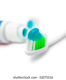 a macro shot of a toothbrush with blue gel toothpaste, which tube is beside