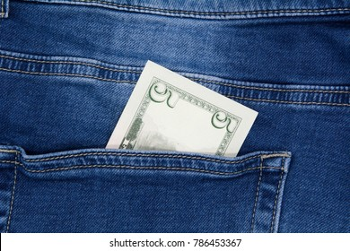 Macro shot of trendy jeans with american 5 dollar bill on its pocket