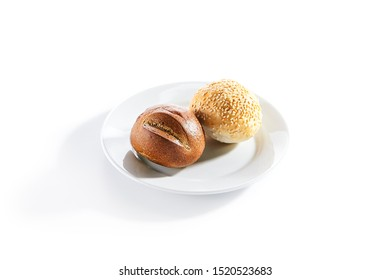 Macro shot of two round buns of rye and wheat flour with sesame seeds top view. Small round brown bread roll and white gluten free bread roll on white restaurant plate isolated