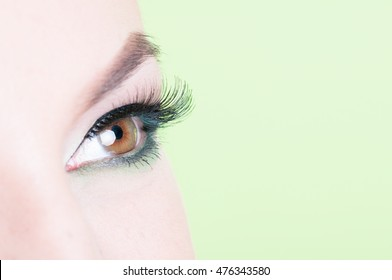 Macro shot of woman eye with lash extension as professional make-up concept isolated on green background with copy text space