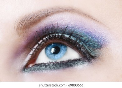 Macro shot of woman eye with violet and blue bright make-up