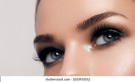 Macro shot of woman's beautiful eye with extremely long eyelashes. Sexy view, sensual look. Female eye with long eyelashes