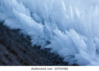 macro shot of a wooden fence covered with ice crystals due to the hoarfrost in winter