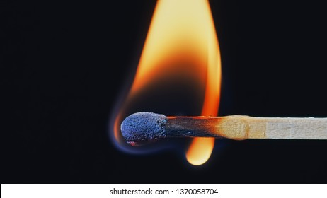 Macro shot of a wooden safety matchstick burning with a bright colorful flame.