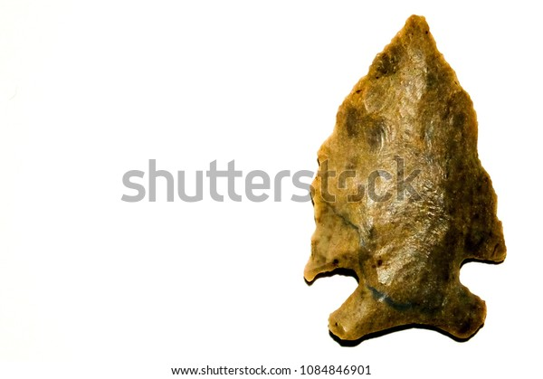 Macro of a single Native American arrowhead from the Elk River watershed in middle Tennessee on solid white background. Room for text.