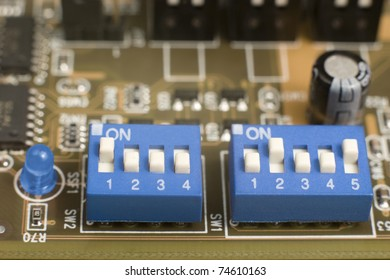 macro of small blue switches and blue led on circuit board