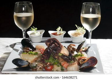 Macro still life white dish with seafood and wine glasses with white wine on a white tablecloth in a studio on a black background