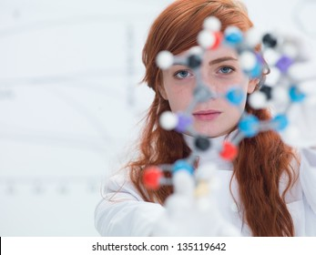 macro of a student in a chemistry lab holding in hands and analyzing DMT molecular model