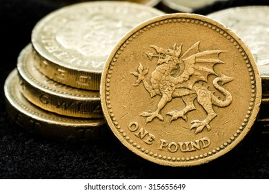 Macro studio shot of different British pound Coins including the Welsh Dragon, Queen Elizabeth's Head and Latin text on a black background