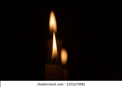 Macro of three candle flames with a dark background.
