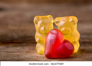 8774634a1301e3 macro two yellow gummy bears with red hearts on wood